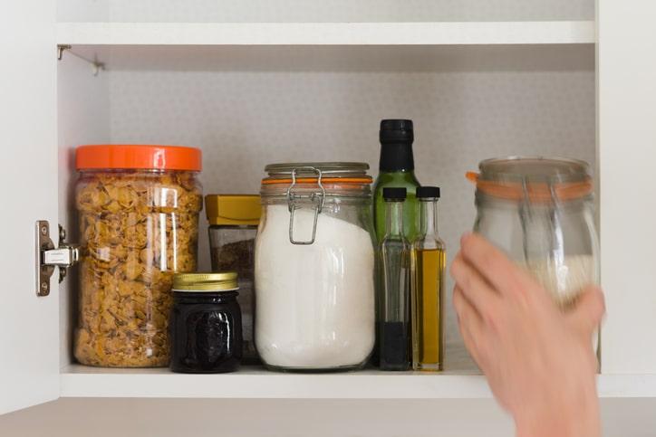 organized jars in white kitchen cabinet