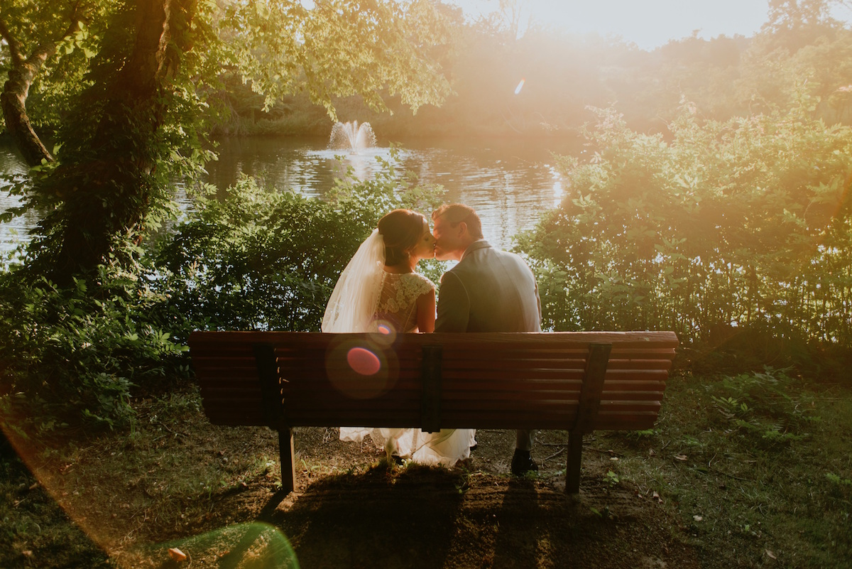 Couple kissing on bench for wedding