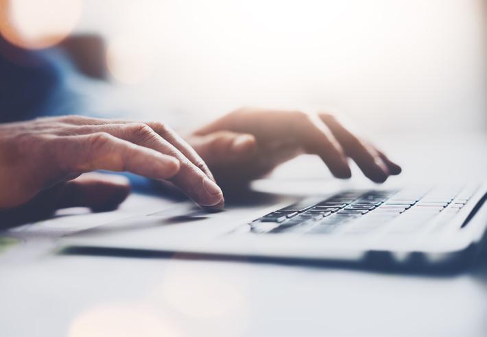 closeup of hands using laptop