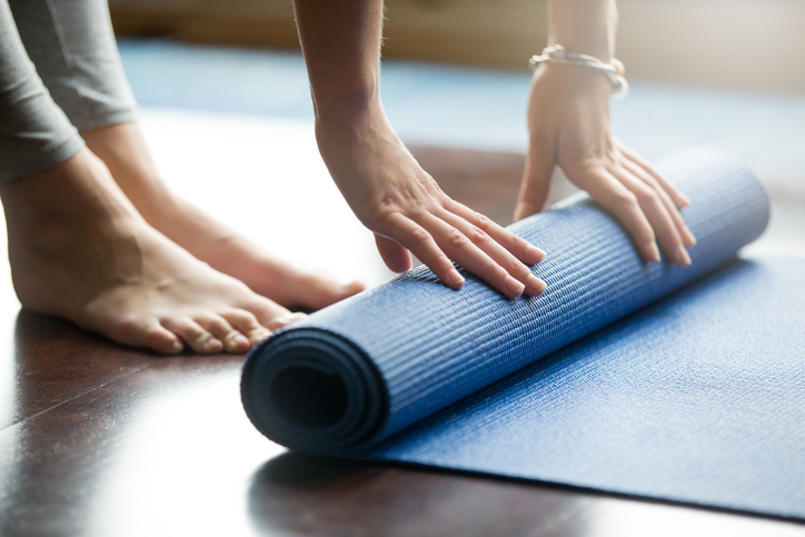 Rolling out a yoga mat to exercise