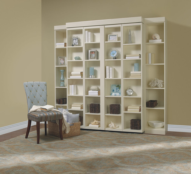 White bookshelf with blue decorations hides a Murphy bed.