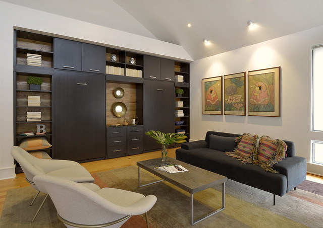 Living space with hidden Murphy beds in dark storage cabinetry.