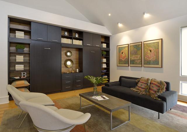 Living space with hidden Murphy beds in dark storage cabinetry.