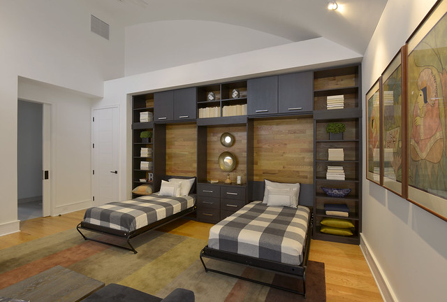 Two Murphy beds pulled down surrounded by dark custom storage cabinetry.