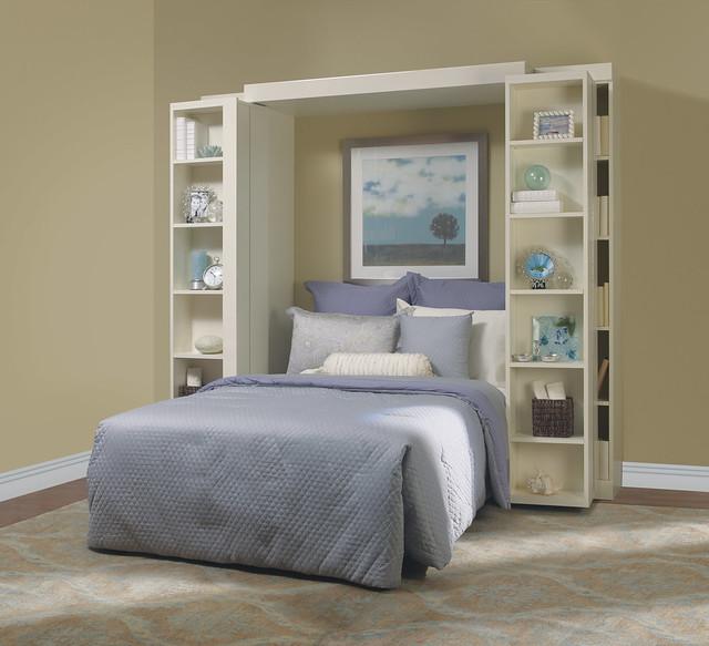 Murphy bed pulled down from white custom bookshelf
