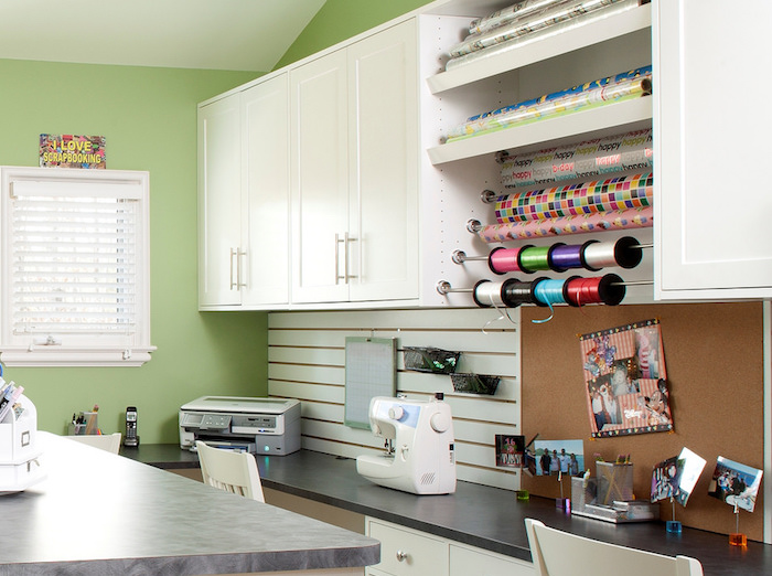 A crafting station with wall mounted paper roll holders, slatwall panels and a work counter.