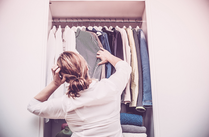 Choosing clothes in closet to store