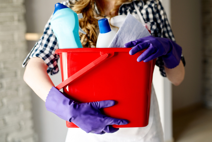 Woman holding bucket of cleaning supplies