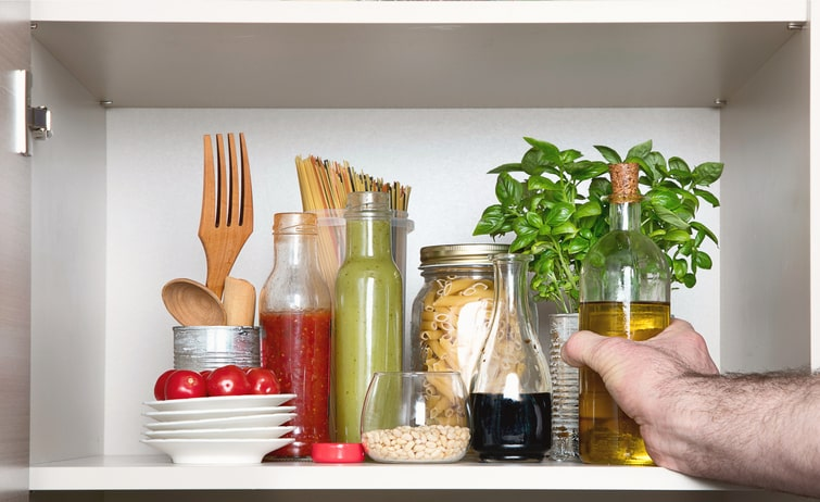 Hand reaching into kitchen pantry with Italian food products.