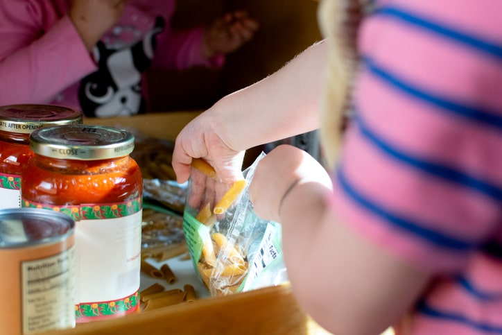 Two kids playing with pasta and pasta sauce in a kitchen cupboard