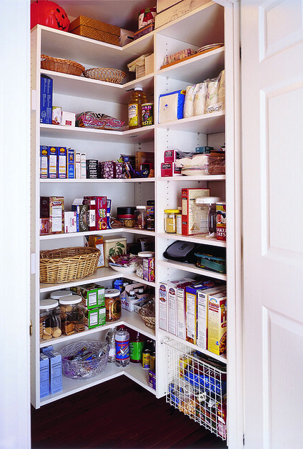 A pantry with a white finish storing lots of organized food