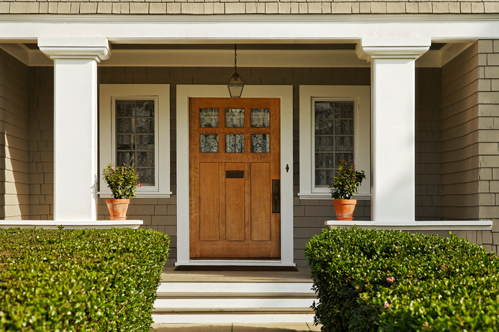 exterior of home entryway with gray paint and natural door.