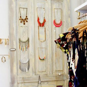 A closet door with hanging necklaces on the back side.