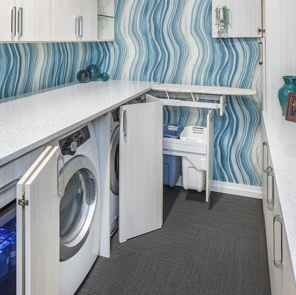 A laundry room with fold out ironing board and cabinet storage.