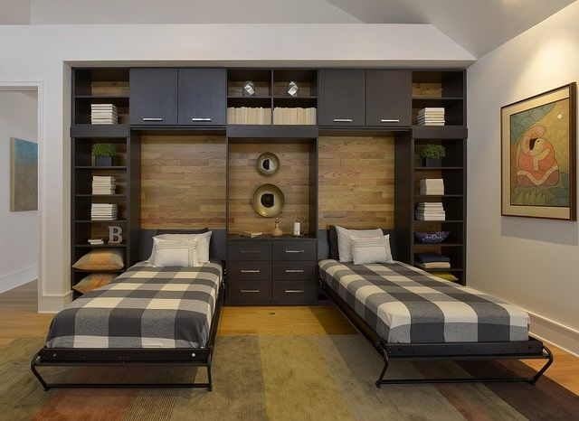 Two wall beds that fold up into a custom cabinet system are shown.
