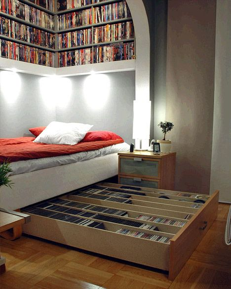 A bed with sliding drawers full of books underneath