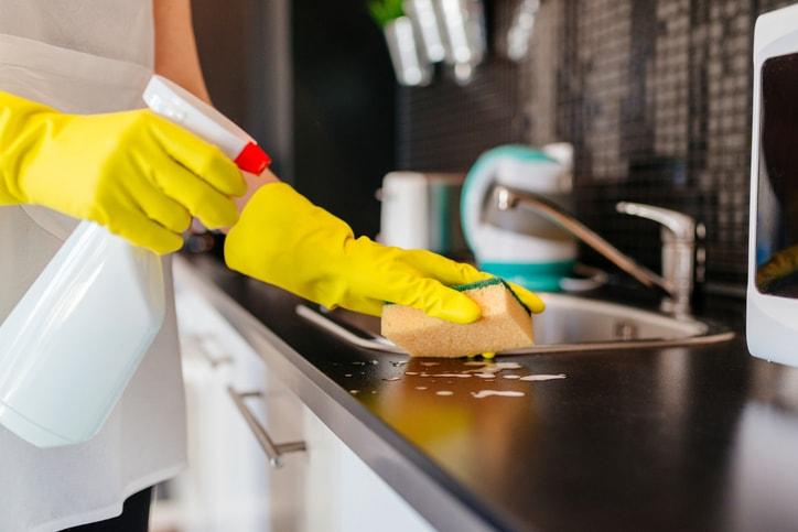 Gloved hands cleaning around a kitchen sink