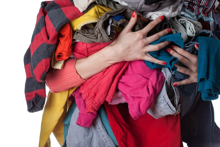 woman decluttering holding pile of clothes in arms