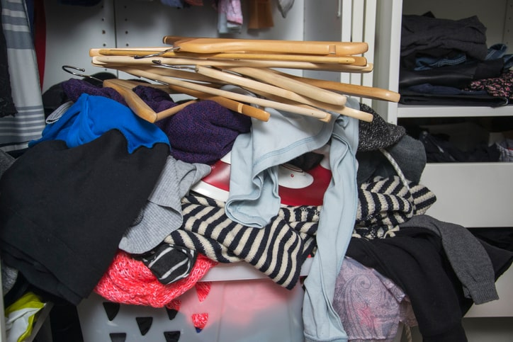 pile of clothes in a basket to declutter closet