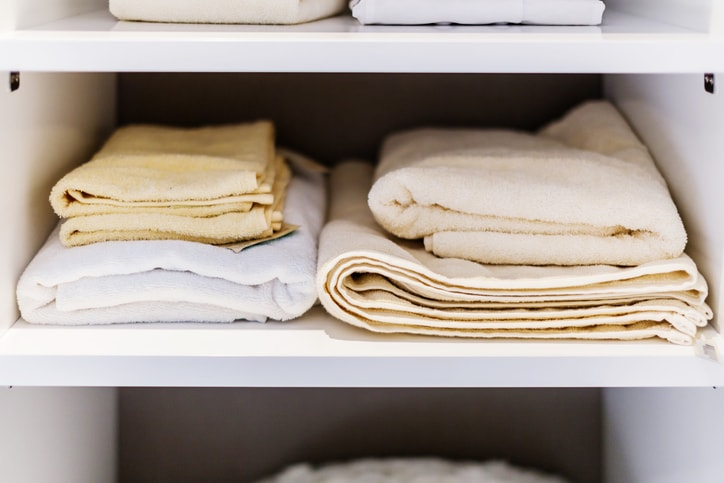 small tidy stack of sheets in linen closet