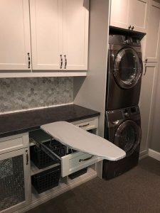 organized laundry room with stacked machines