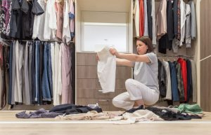 woman sorting and organizing clothes in closet