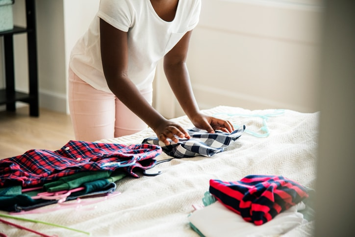 teen girl folding clothes on a bed
