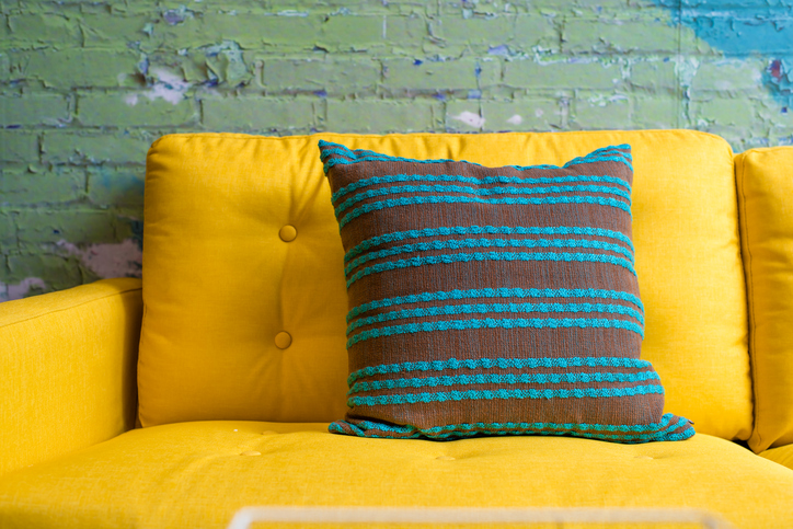 Bright yellow couch with patterned pillow