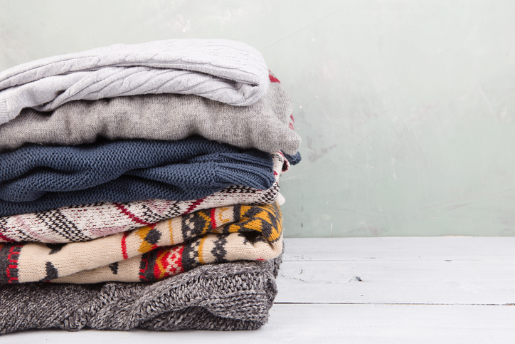 Stacked winter clothes sweaters for storage